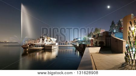 Night cityscape embankment on the river with a pleasure boat in the full moon