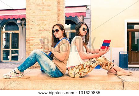 Girlfriends couple reading text on phone and book - Female hipster friends sitting back to back using phone and holding travel guide - Concept of learning and knowledge by modern and traditional media