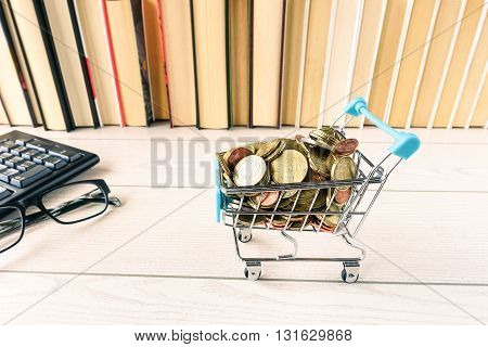 Trolley with coins on office wood desk background keyboard books -Closeup cart with euro cents - Modern concept of global business trade and shopping online - Symbol of e-commerce and internet market