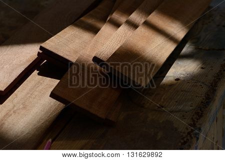 Boat building planks on a workbench in the shade