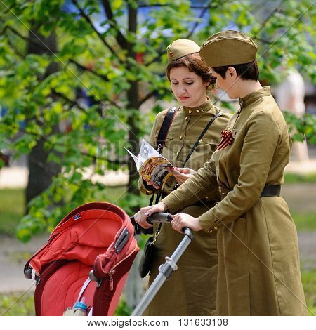Orel Russia - May 9 2016: Celebration of 71th anniversary of the Victory Day (WWII). Two military moms with red stroller looking at book