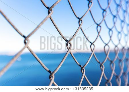 steel net with landscape of sea in blue sky