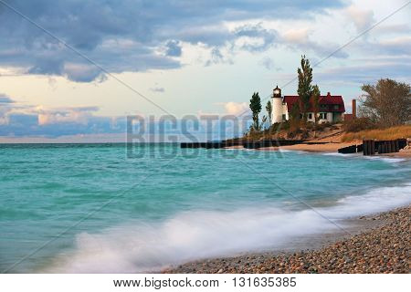 Point Betsie Lighthouse flashes over a stormy beach near Frankfort Michigan. A wave crashes to shore and a late day sky create a dramatic scene around this popular Michigan lighthouse