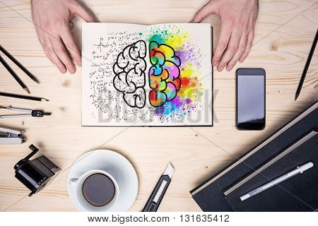 Top view of wooden desktop with coffee cup stationery items smart phone and hands holding notepad with creative and analytical brain sides sketch