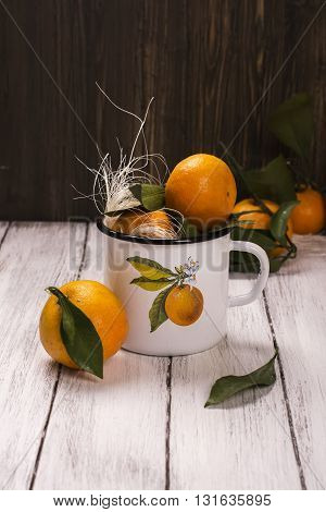 Tangerines in white enamel retro mug over wooden background. Toned image. Selective focus
