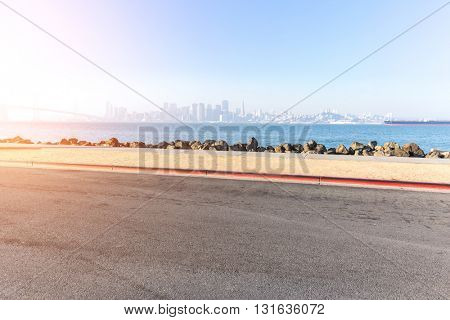asphalt road near sea with cityscape and skyline of san francisco
