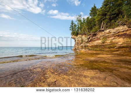 Rocky outcroppings define the shoreline of Pictured Rocks National Lakeshore near Au Train Michigan. The Lake Superior shoreline is rugged and wild. Grand Island is shown in the distance.