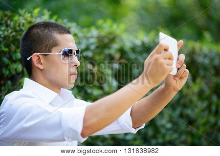 Young Man In Sunglasses Taking Selfie Through Tablet
