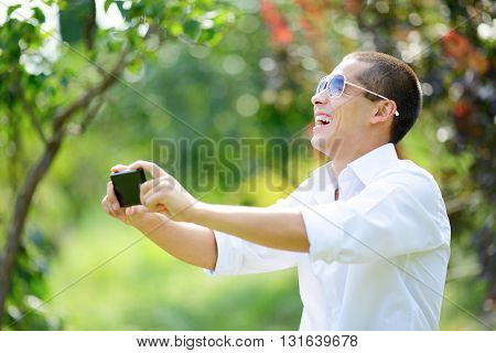 Laughing Young Man In Sunglasses Taking Selfie