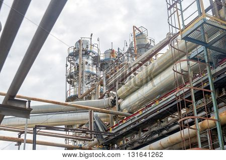 Industrial equipment and pipelines at the gas processing plant on a summer day