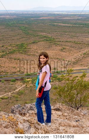 A young girl who looks confident and proud of her accomplishment stands at the top of a small mountain that she has climbed.  It is a desert mountain and if you zoom in there are a bunch of flying ants behind her, starting to swarm.