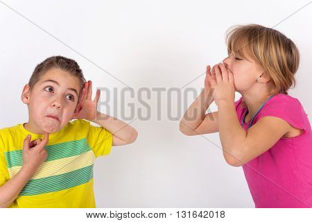 Boy cupping his hand behind ear because he cant hear the girl