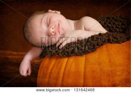 Happy newborn sleeping in pumpkin.  He is smiling in his sleep with his arm hanging over the edge of the pumpkin.  The image has been textured for a more artistic look.