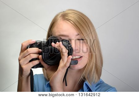 Young Pretty Woman With Digital Camera On Gray Background