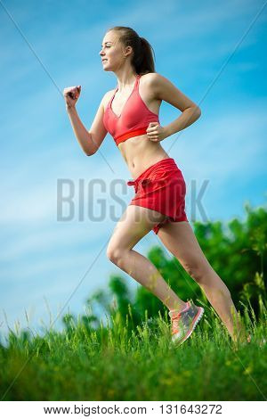 Young lady running. Woman runner running through the summer park rural road. Workout in a park. Beautiful fit girl. Fitness model caucasian ethnicity outdoors. Weight loss exercise. Jogging.