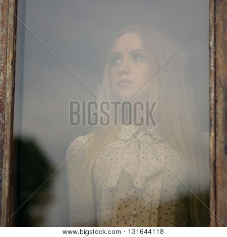 portrait of a beautiful girl looking through window