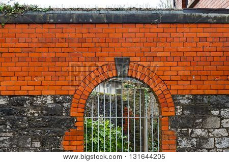 Photo of a high wall and lattice gate