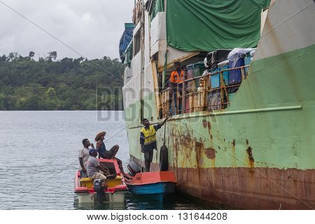 Seghe, Solomon Islands - June 16, 2015: Ship anchored at Seghe harbor with people trading goods.