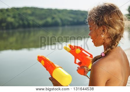 Girl playing with a squirt gun at a lake on the summer holidays