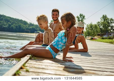 Family on a holiday at a lake in summer cooling their feet