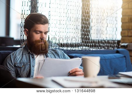 Much task to do. Pleasant concentrated bearded man sitting at the table and working with papers while being involved in work