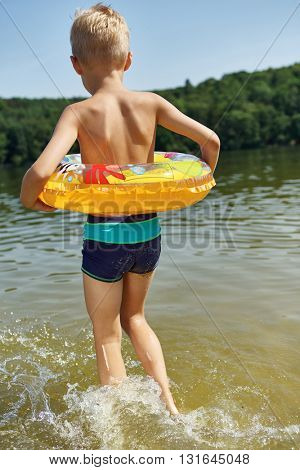 Kid from the back splashing water with a floating ring on the holidays