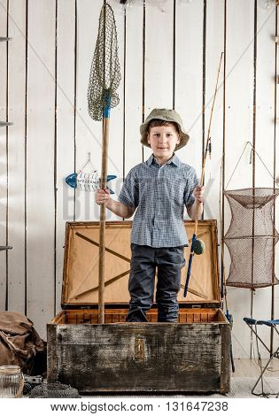 little boy in hat standing in opened chest with fishing rod in hands