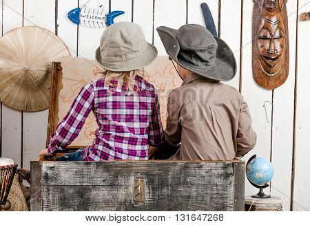two little children in sitting in old chest study map on the wall