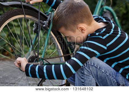 Little caucasian schoolboy repair bicycle at outdoor