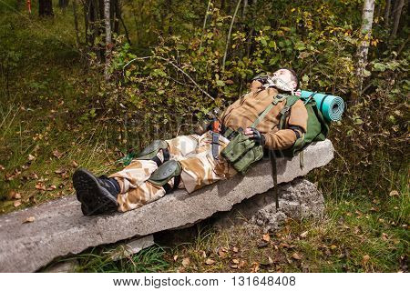 Soldier relaxing on reinforced a concrete slab.