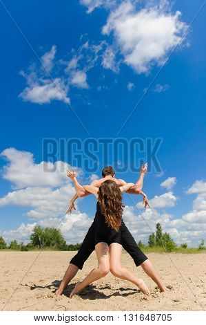 Contemporary dance. Man and woman in passionate dance pose on beach. Young couple dancing modern dance in beautiful pose outdoors. Man with naked torso on sand.