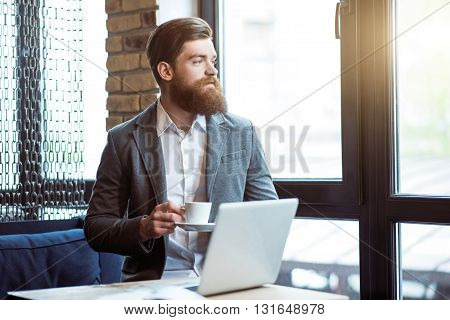 Nice view. Pleasant delighted positive man holding cup and standing in the office while looking in the window