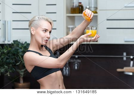 sport woman Freshly squeezed orange juice at home