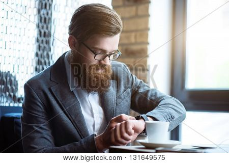 Positive atmosphere. Pleasant content bearded man sitting at the table and smiling while using his smart watch