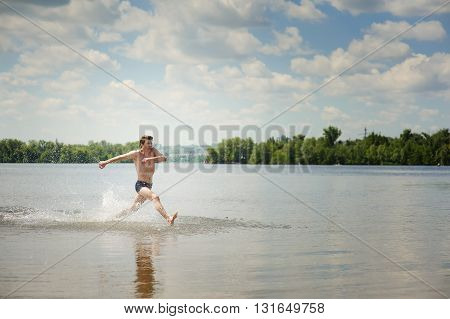 Man running through shallow water towards beach. Man is splashing water. Young man smiling, active on a river beach.