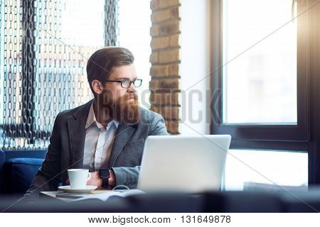Serious attitude.   Pleasant concentrated bearded serious man sitting at the table looking aside while being involved in thinking