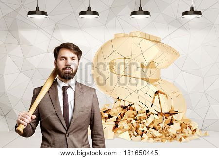 Businessman with bat has just broken a huge golden dollar sign in room with patterned concrete wall and lamps. Currency concept