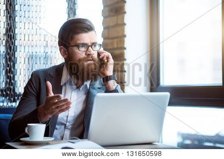 Listen to me. Serious pleasant bearded man sitting at the table and using gesture while talking on cell phone