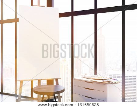 Blank easel stool and counter with paint palette in interior. Framed window with New York city view in the background. Toned image. Mock up 3D Rendering