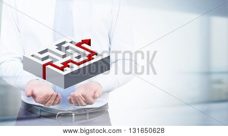 Solution concept with businessman holding abstarct maze with red arrow going through it on blurry background
