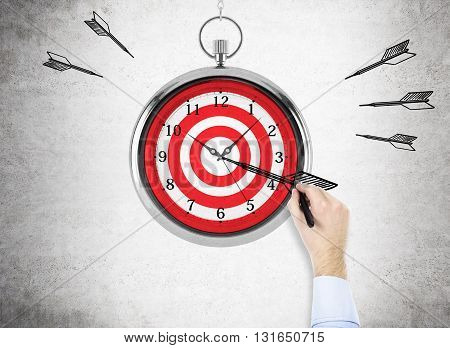 Time management and targeting concept with businessman hand drawing a dart on abstract dartboard clock on concrete background