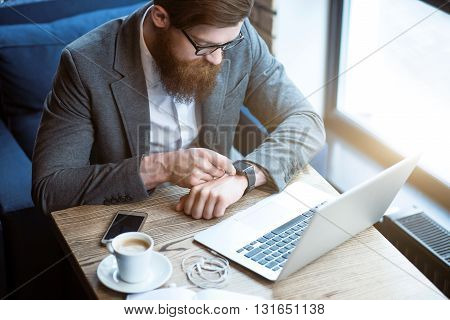 Check it. Pleasant bearded man sitting at the table and using his smart watch