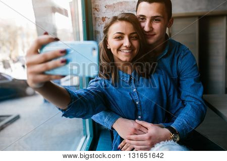 handsome guy and beautiful girl making selfie indoors by the window