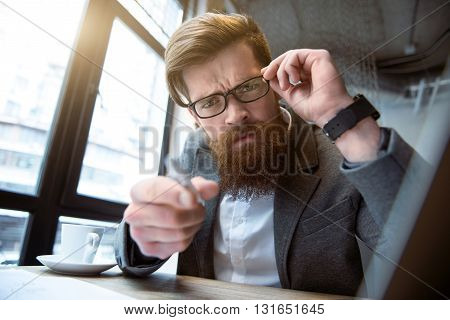 Furious glance. Emotional  brutal man sitting at the table and touching his glasses while pointing you