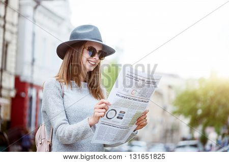 What is up. Smiling and merry young woman reading some articles in a newspaper while being in a bid modern city