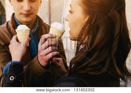 handsome guy and pretty girl posing with ice cream on background wall
