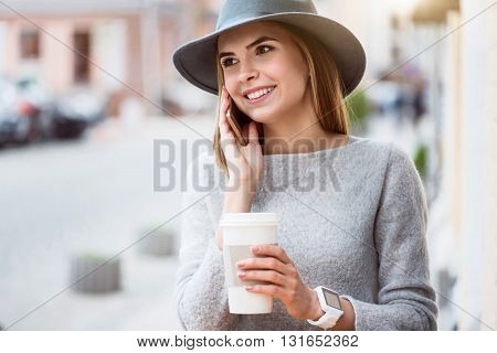 Waging tongue. Happy and merry young woman speaking per cell phone with her friend while drinking nice coffee