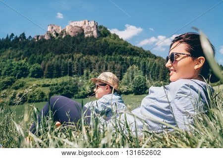 Mother with son rest together on green medow with view on old castle