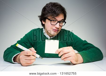 Crazy young man in green pullover sitting at white desk with blank paper sticker and marker in hand and raising eyebrows