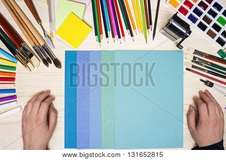 Man's hands next to colorful paper sheets and drawing tools on wooden table. Top view Mock up